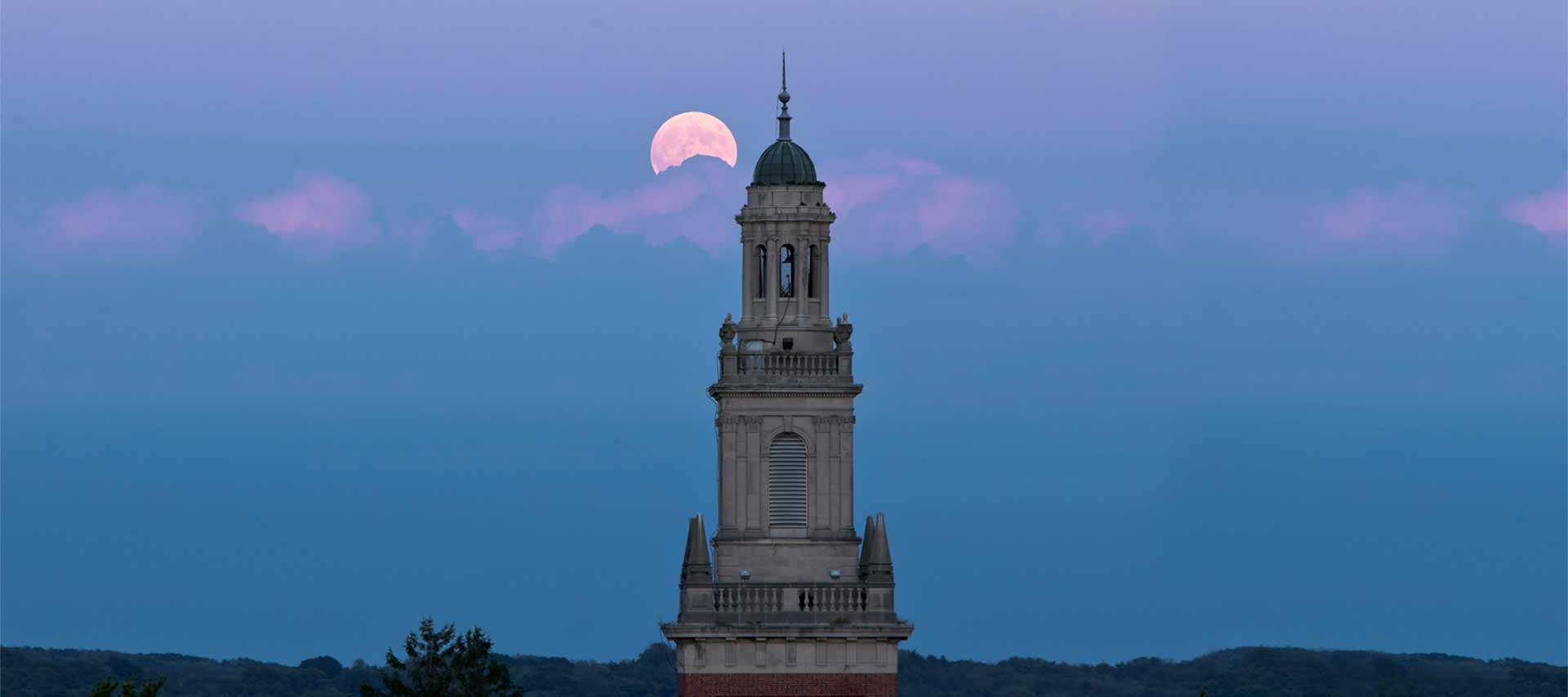 The bell tower of Swasey Chapel at twilight with a full moon in the background