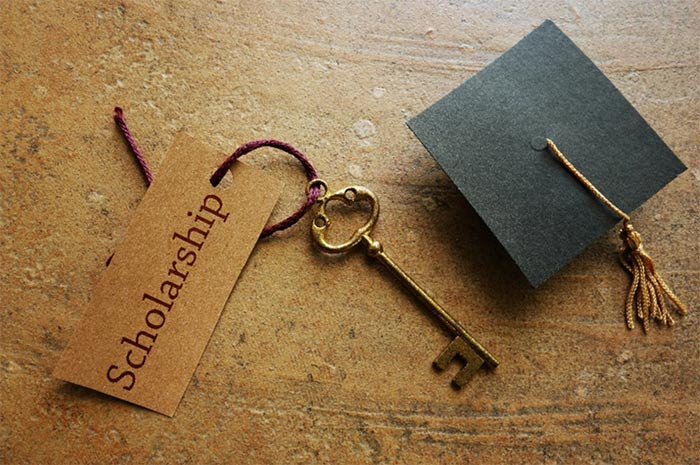 "A photo of a skeleton key tagged ""Scholarship"" next to a mortarboard"